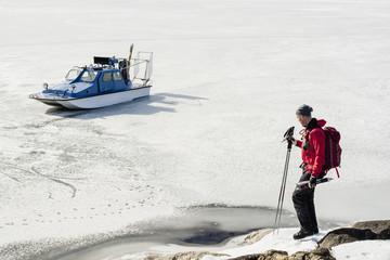 Man holding ski poles with speedboat on frozen lake