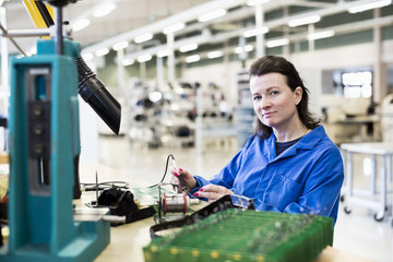 Portrait of confident female technician working on circuit board at desk in industry