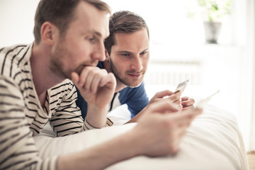 Homosexual couple looking at credit card while lying in bed at home