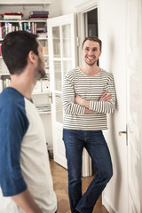 Young gay man standing arms crossed while looking at partner in house