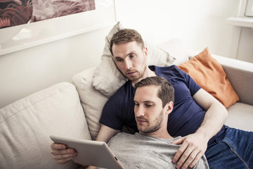 Young homosexual using digital tablet together while relaxing on sofa at home