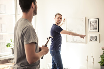 Side view of young gay man looking at partner while hanging frame on wall in home