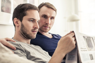 Homosexual couple reading newspaper together at home