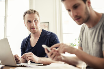 Young gay man looking at partner using mobile phone at table in house