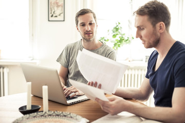 Gay man reading paper while partner using laptop at table in home