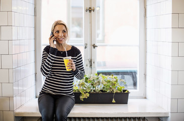 Mid adult businesswoman using mobile phone while holding disposable cup in office restaurant
