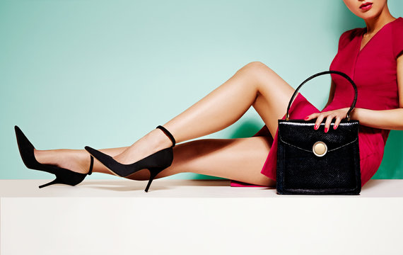 Beautiful legs woman with black high heels shoes and handbag purse. sitting on white table. Isolated on light green background.