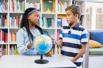 School kids discussing with each other in library