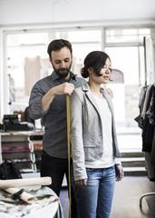 Mid adult male fashion designer measuring woman's shoulder at studio