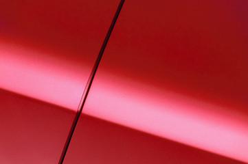 Surface of red sport sedan car, detail of metal fender and door of vehicle bodywork
