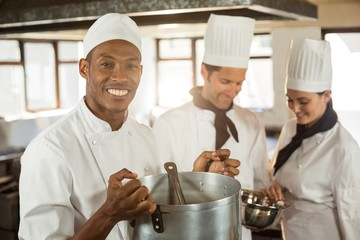 Portrait of smiling chef holding a cooking pot