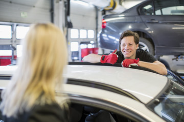 Confident young mechanic showing thumbs up to female customer over car