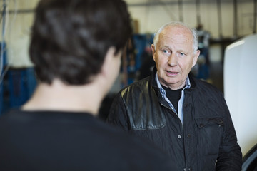 Senior male customer discussing with mechanic at workshop