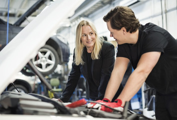 Male mechanic discussing with female customer while repairing car engine at workshop