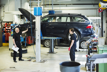 Male mechanics discussing while standing against car jack at workshop