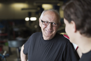 Happy senior male mechanic smiling at coworker in auto repair shop