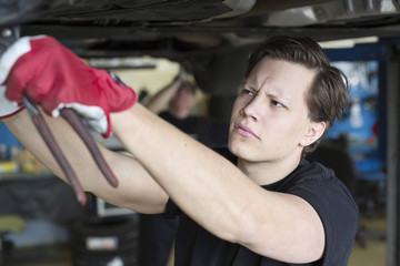 Young male mechanic repairing car from below with coworker in background at workshop