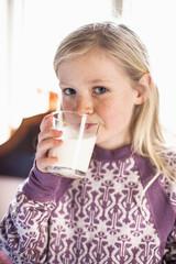 Portrait of little girl drinking milk