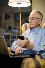 Senior man using laptop, mobile phone and digital tablet while sitting on armchair