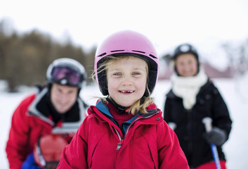 Portrait of little girl in ski-wear smiling with family in background