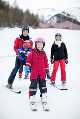 Portrait of happy little girl in ski-wear standing with family in background