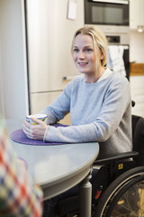 Disabled mid adult woman in wheelchair looking at friend in kitchen