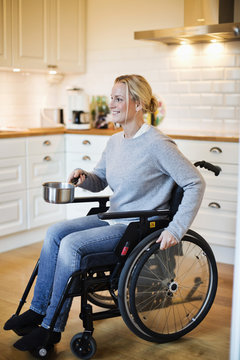 Happy disabled mid adult woman in wheelchair holding saucepan at kitchen