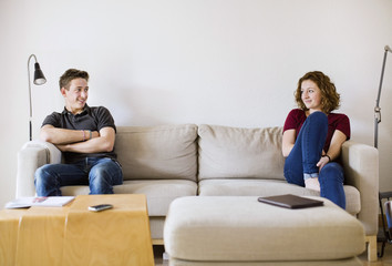 Teenage boy and girl looking at each other while sitting on sofa