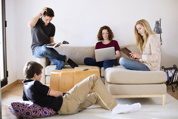 Young friends with magazine, laptop and digital tablet in living room