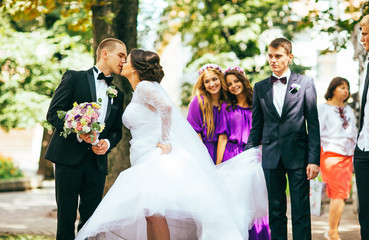 Newlywed couple, bridesmaids & groomsmen having fun outdoors. Bridesmaids in purple (violet) dress. Walking in the city.