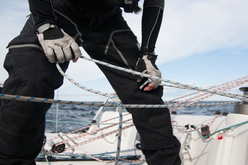Midsection of man tying rope of sailboat