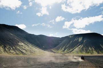 People riding vehicles against mountain range, Iceland