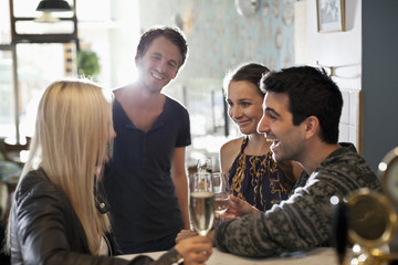 Group of happy friends holding wine glasses in saloon