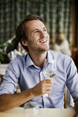 Happy young man holding wine glass at restaurant table while looking up