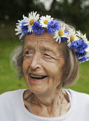 Close-up of happy senior woman with wreath of flowers on her head