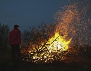 Man standing in front of Walpurgis night bonfire