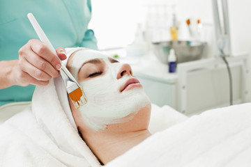 Young woman receiving a beauty treatment with make-up brush in health spa
