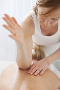 Mature therapist massaging mid adult woman's back with elbow