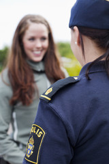 Happy woman looking at female police officer
