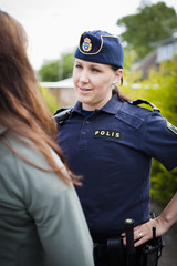 Female police officer talking to woman at work