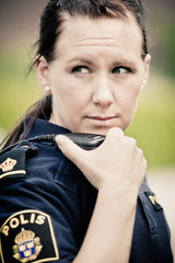 Close-up of confident female police officer using CB radio
