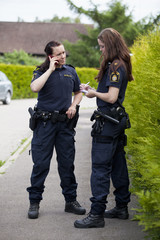 Female police officer writing notes while colleague using cell phone
