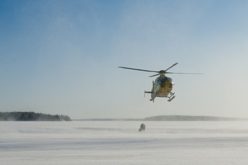 Rescue helicopter landing with person on ice rink