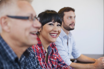 Businesswoman with colleagues smiling in office meeting