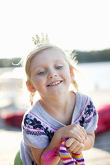 Cheerful girl wearing crown smiling outdoors