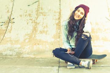 Hipster skateboarder girl with skateboard outdoor sitting at skatepark