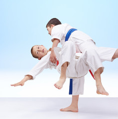 Boys are trained judo throws on a light background