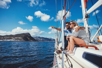 Young couple sitting on boat looking at a view