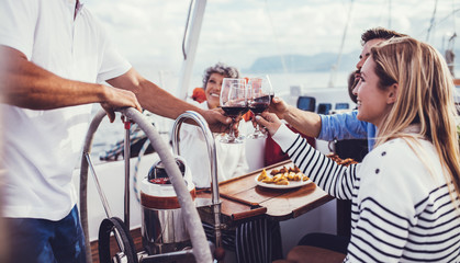 Friends toasting with red wine on yacht