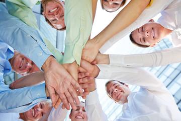 Hände stapeln als Symbol für Teamwork